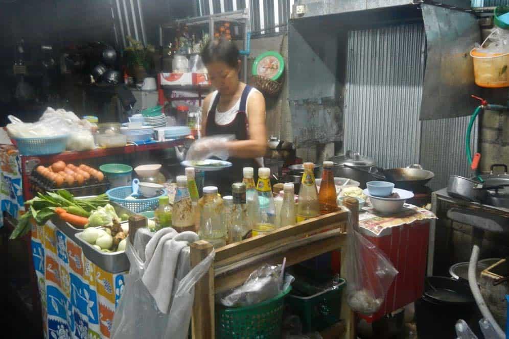 Mujer cocinando en un garaje, Chiang Mai, Tailandia