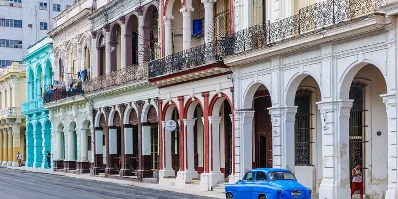Coche azul en frente de casas coloniales a La Habana, Cuba. Viaje a Cuba